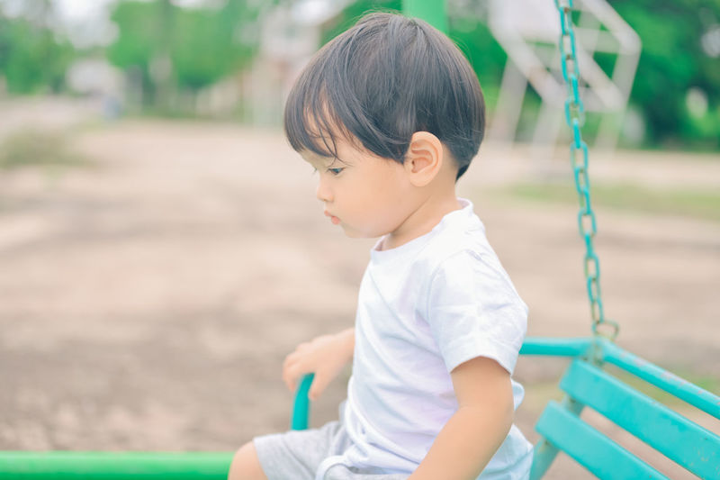 Side view of boy looking away in playground