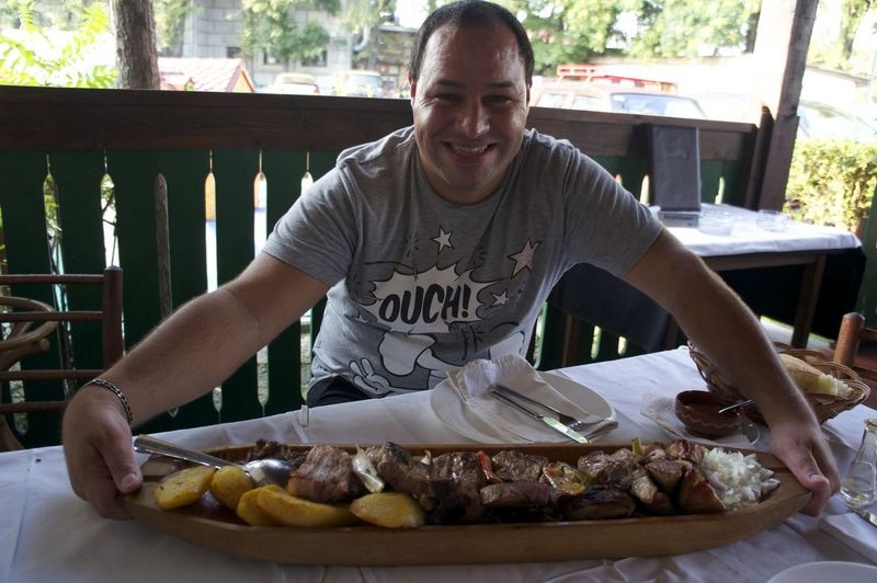 Portrait of man with large serving board at table