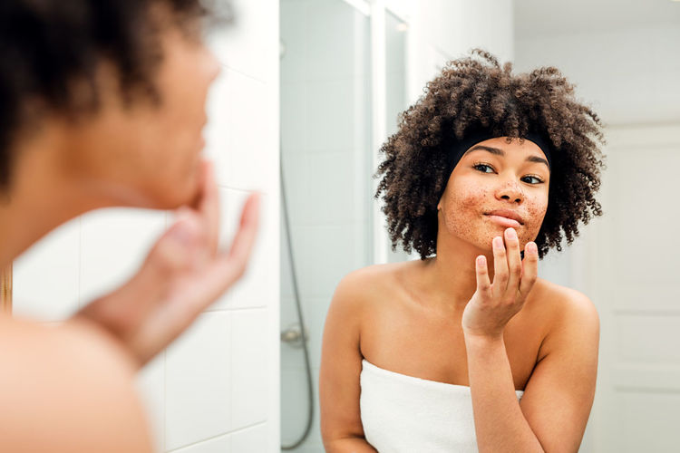 Indoors  Young Women Curly Hair Lifestyles Bathroom Beautiful Woman Girl Skin Care Natural Beauty Towel Cream Morning Looking Mirror Real People Standing Wellness Portrait African American Females Hand Smiling