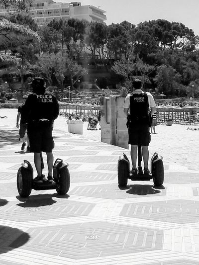 Policia local en la playa Black And White Photography Policia Local Beach Segway Ride Segway Sun Tree Men Full Length City Road Sky