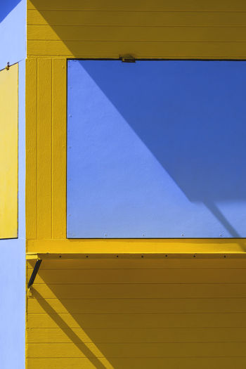 Sunlight and shadow on yellow and blue kiosk