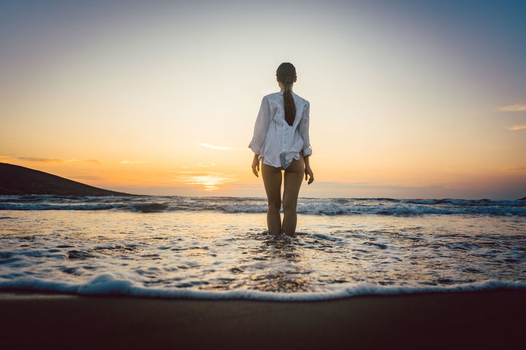 Rear View Of Seductive Woman Standing On Shore At Beach During Sunset