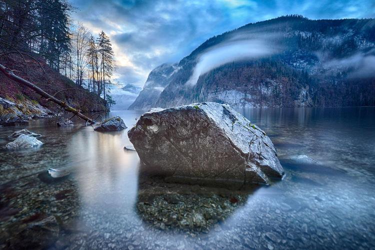 Rock amidst lake against mountain