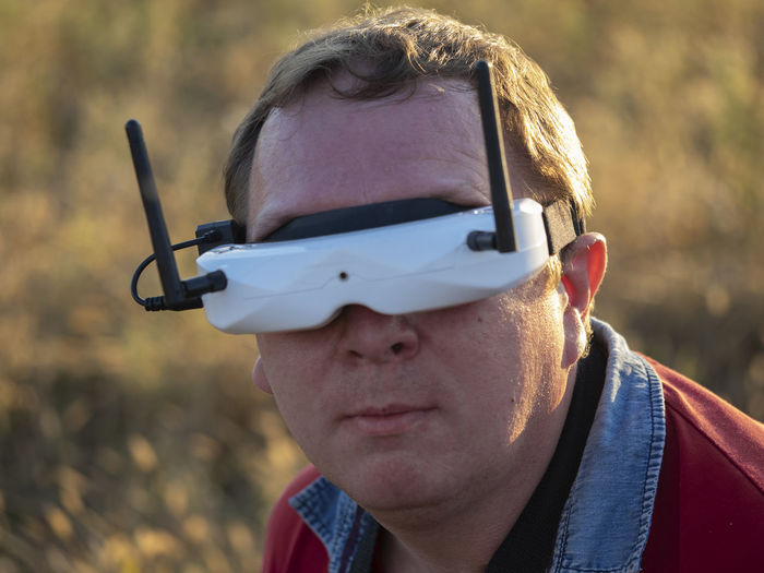 Close-up of man wearing virtual reality against sky during sunset