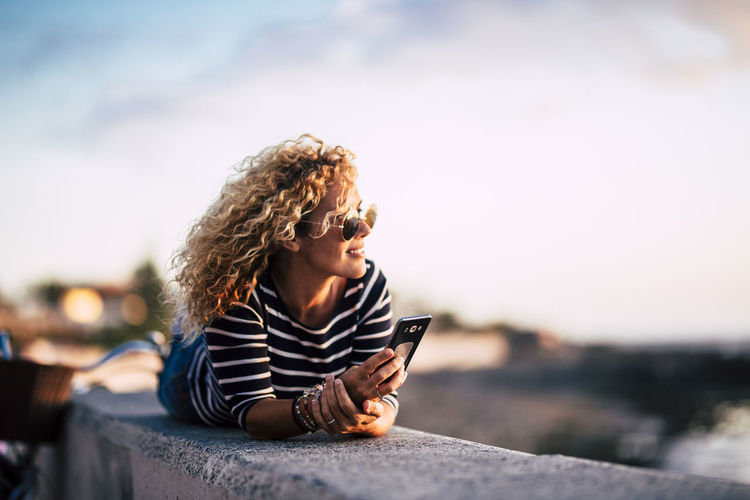 Young woman looking away while sitting on mobile phone against sky