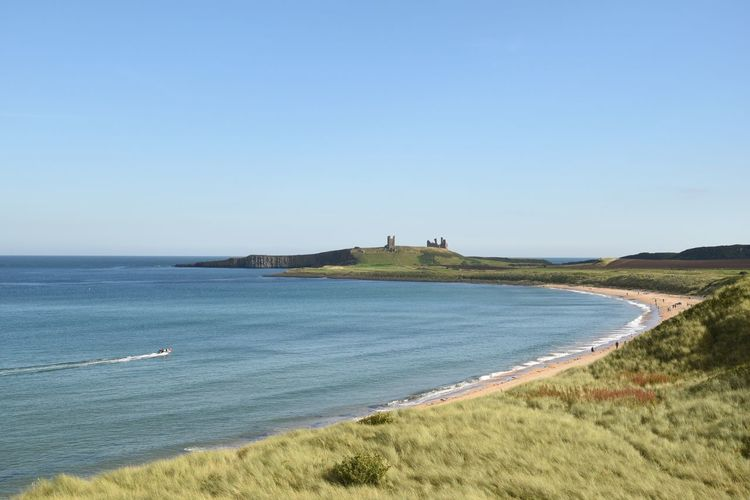 Ruins of Dunstanburgh castle, UK Water Blue Tranquil Scene Sea Clear Sky Tranquility Copy Space Scenics Beauty In Nature Nature Grass Coastline Calm Non-urban Scene Day Outdoors Shore Remote Seascape Green Color Landscape Northumberland Rural Scene Castle Beauty In Nature