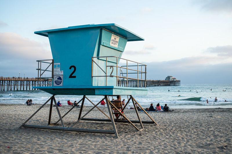 Lifeguard hut on beach against sky