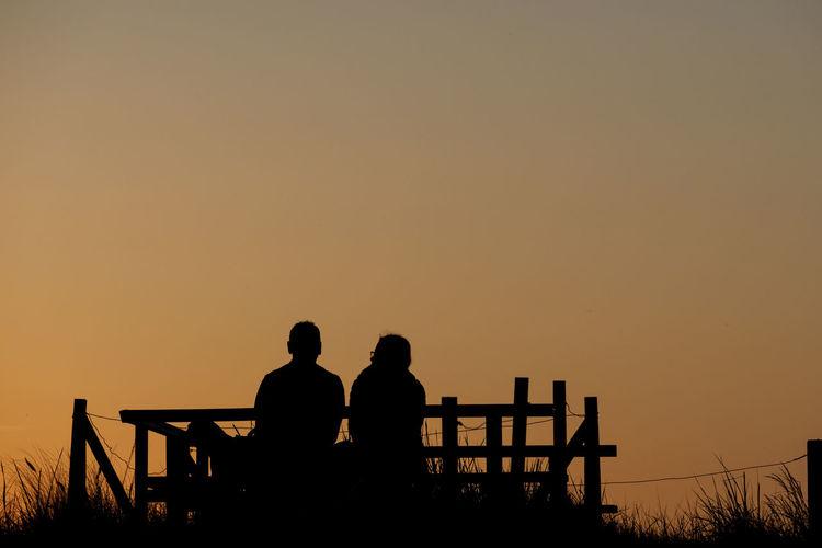 Silhouette men sitting on bench against orange sky