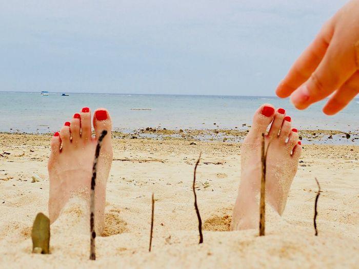 Cropped hand reaching legs at beach