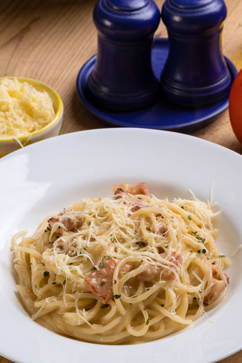 High angle view of spaghetti with carbonara in plate on table