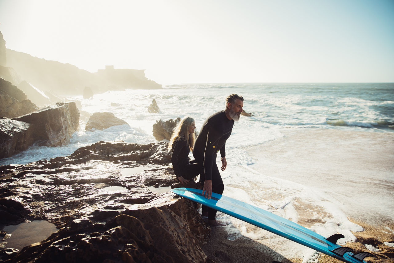 Couple with surfboard at beach