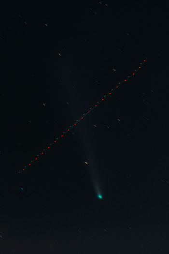 Low angle view of illuminated lights against sky at night with the comet neowise