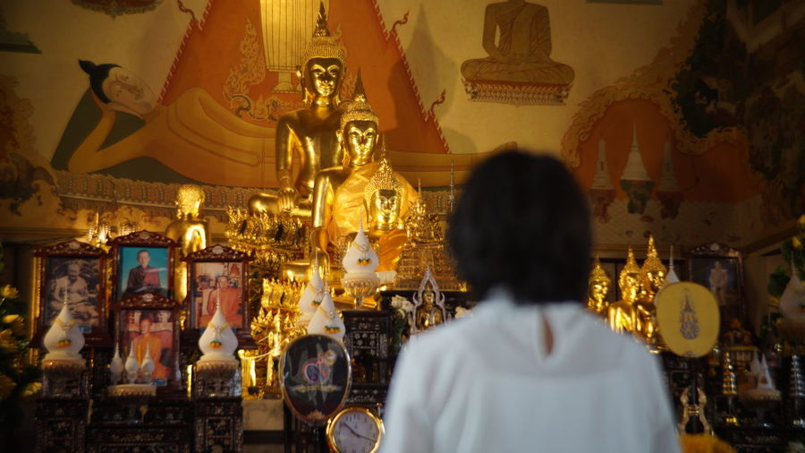 Woman Standing In Front Of Buddha Statues In Temple