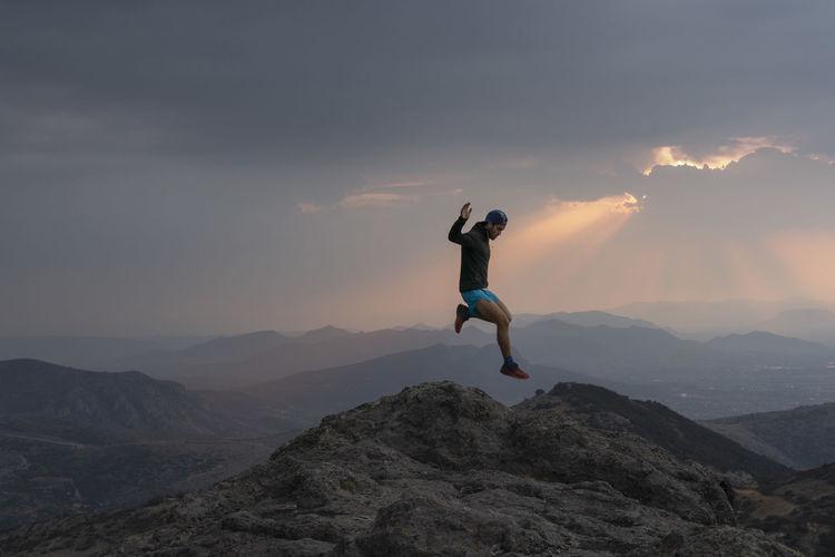 Full length of man climbing rock on mountain against sky