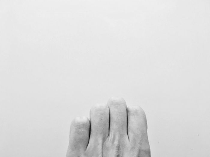 Cropped hand of person against gray background