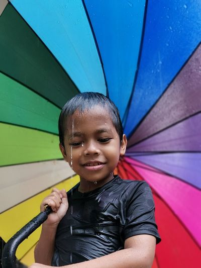 Portrait of smiling boy holding umbrella