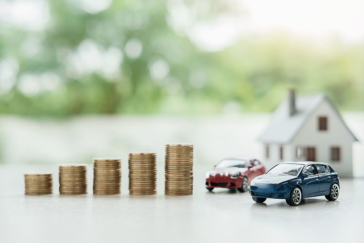 Close-Up Of Toy Cars And Coins On Table