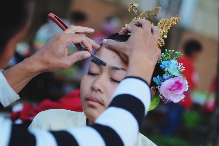 Beautician applying make-up on young woman