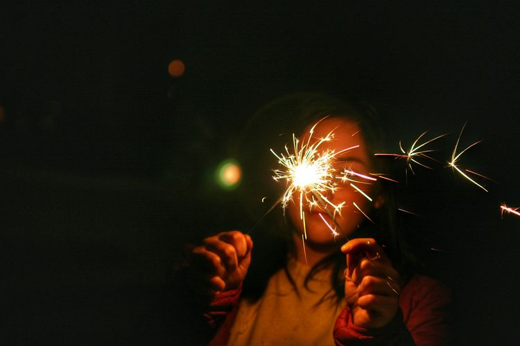 Close-Up Of Girl Holding Sparklers At Night