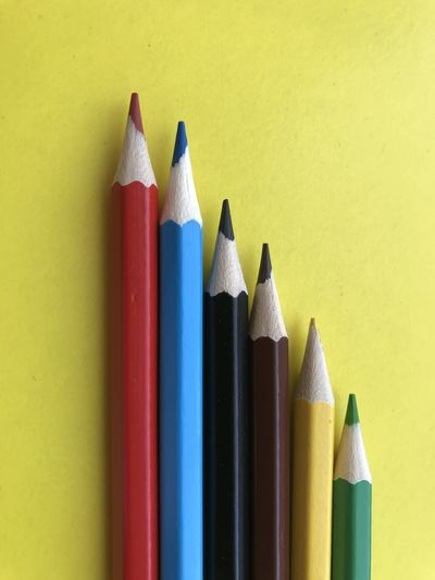 Close-up of colored pencils against yellow background