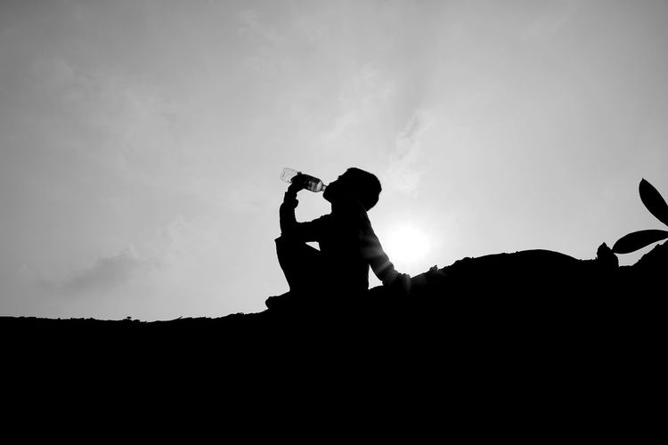 Side view of silhouette boy drinking water from bottle while sitting on land against sky