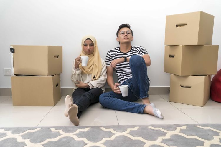 Young Malay Couple take a break after house moving Cardboard Box Sitting Full Length Cardboard Box Casual Clothing Lifestyles Indoors  Front View Real People Young Adult Young Women Couple - Relationship Adult People Two People Young Men Men Togetherness Young Couple Flooring Moving House Tiled Floor