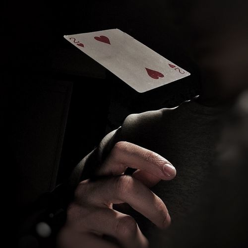 Cropped hand playing cards in darkroom