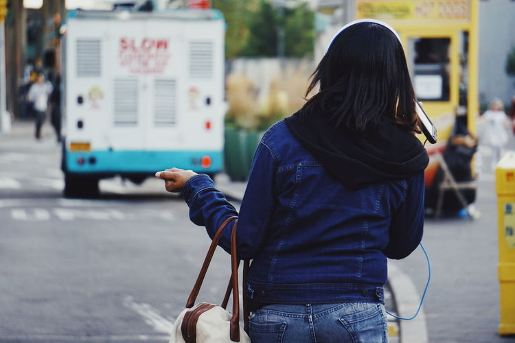 Rear view of woman using mobile phone while walking on street