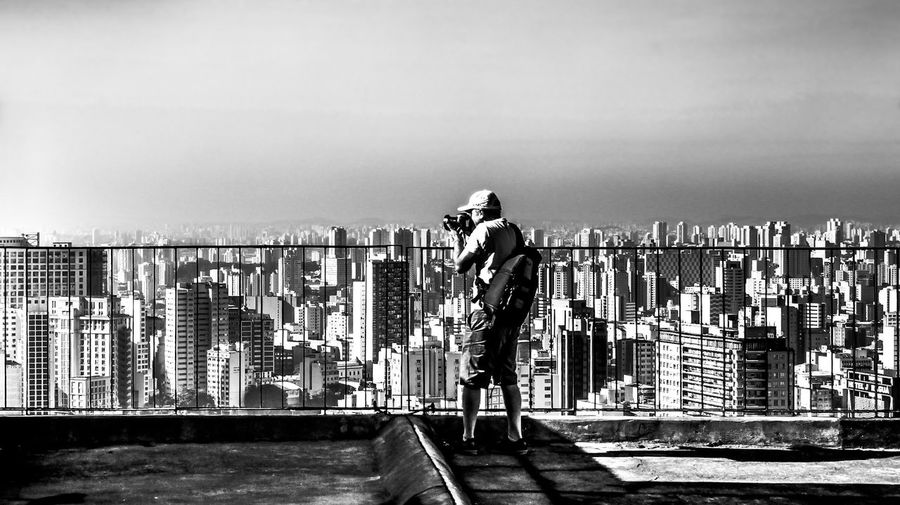 Side View Of Man Photographing Cityscape Against Sky