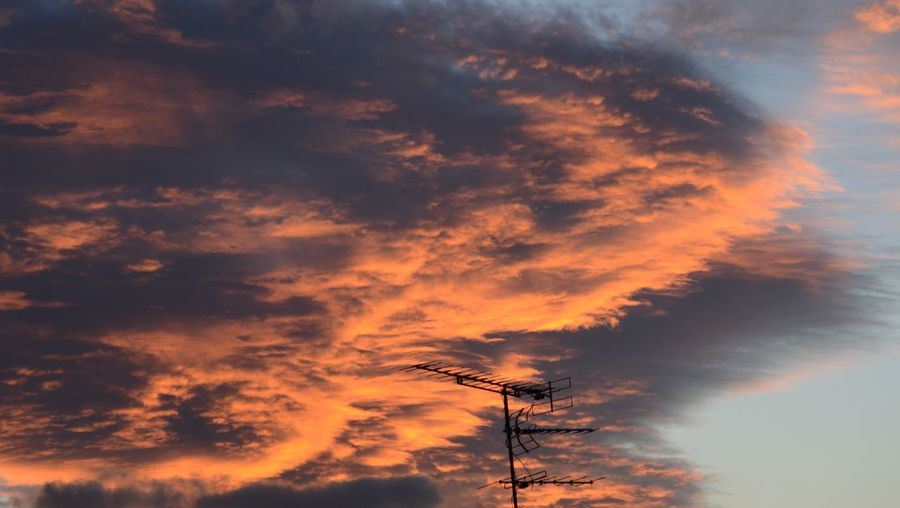 Silhouette antenna against sky during sunset