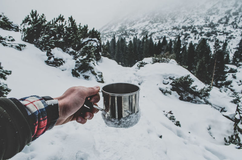 Cropped image of hand holding tea cup against snowcapped mountain