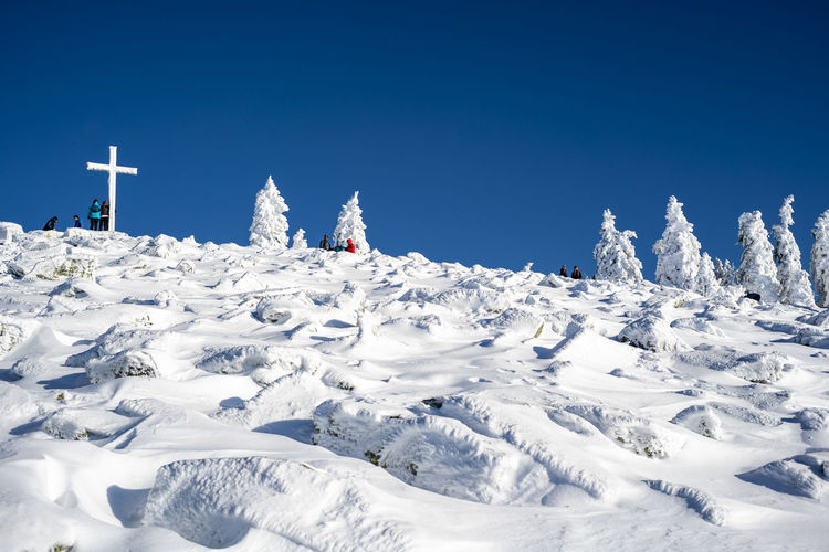Low angle view of people on snow covered land against clear blue sky