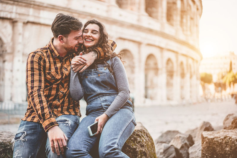 Young couple embracing while sitting against historical building