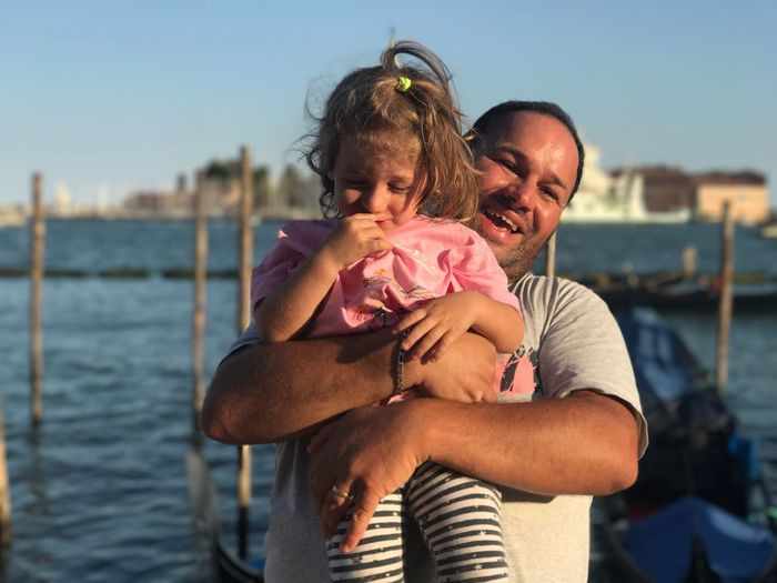 Portrait of man holding daughter while standing against grand canal