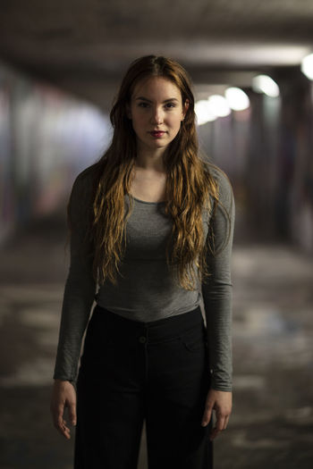 Portrait of young woman standing in tunnel