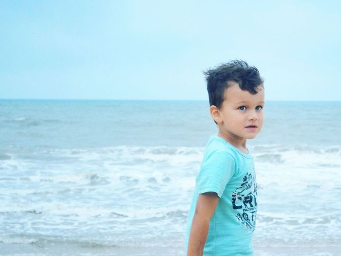 Side view of boy standing at beach