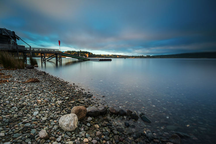 Lake Te Anau Water Sky Nature Sea No People Tranquility Tranquil Scene Architecture Scenics - Nature Outdoors Te Anau Lake Te Anau Long Exposure New Zealand Jetty Rock Solid Stone - Object Cloud - Sky Rock - Object Stone Pebble Beauty In Nature Beach Land Bay