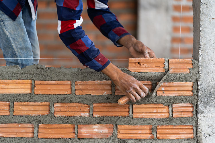 Man working on wood against brick wall