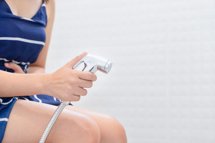 Midsection of woman with hands on stomach holding shower while sitting in bathroom