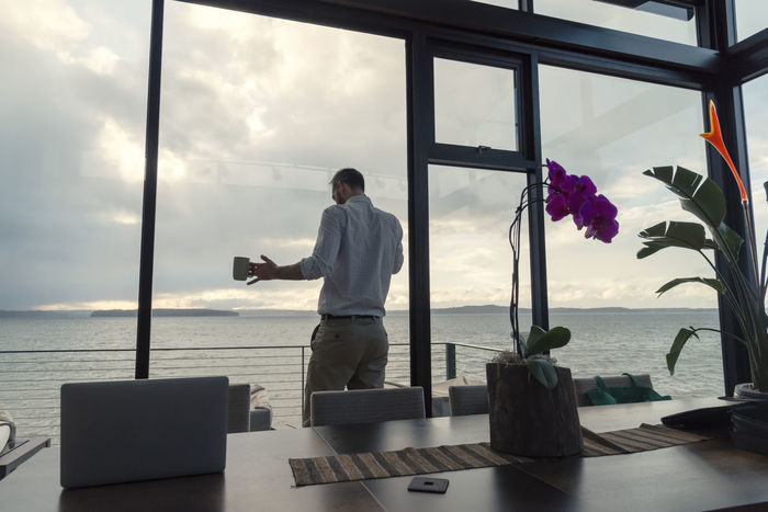 Rear view of man holding coffee while talking on the phone by his desk over looking the sea and cloudy sky. Home Office Morning Negotiating Rear View Cloud - Sky Coffe Day Full Length Horizon Over Water Indoors  Men Nature One Man Only One Person People Professional Real People Sea Sky Standing Technology Telecommute Water Window Wireless Technology