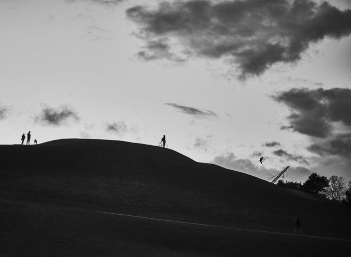 Silhouette people walking on landscape against cloudy sky