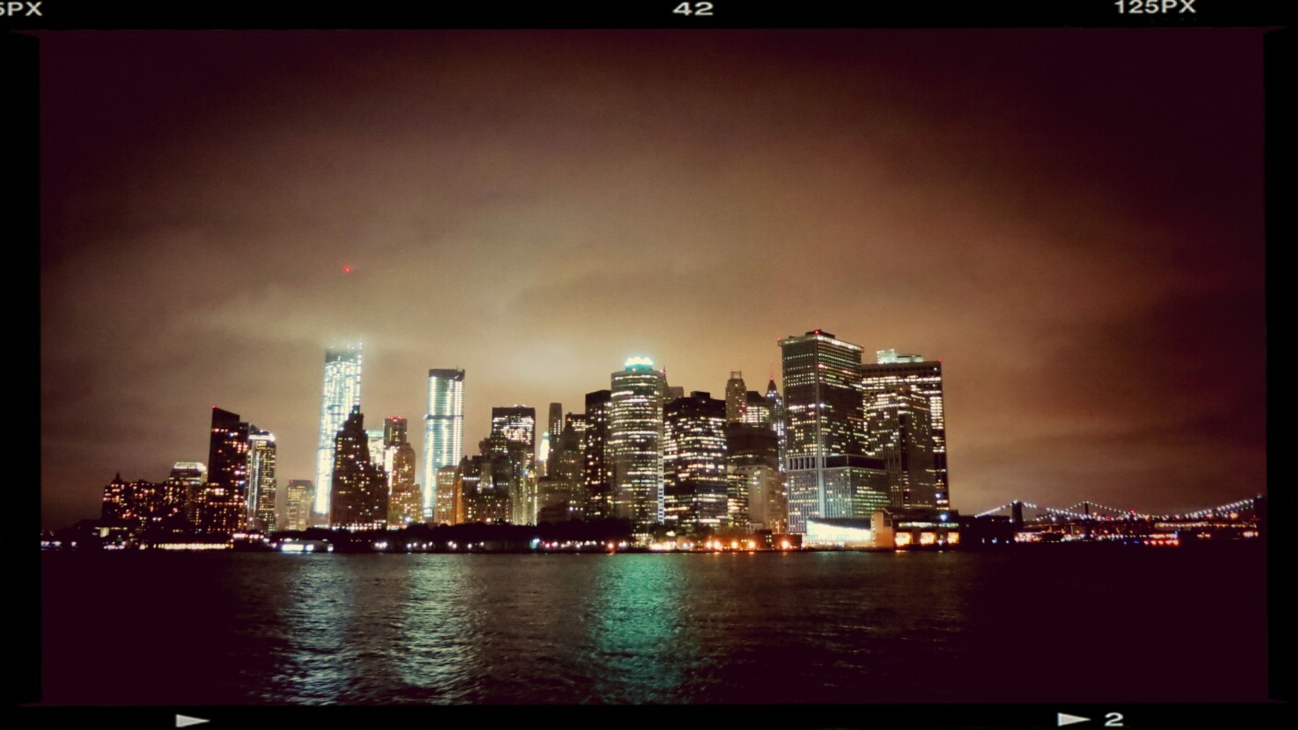 illuminated, city, water, building exterior, cityscape, architecture, waterfront, night, built structure, sea, transfer print, skyscraper, sky, urban skyline, auto post production filter, river, reflection, modern, skyline, dusk