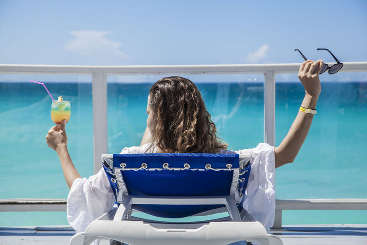 Rear view of woman having drink while relaxing on lounge chair against sea