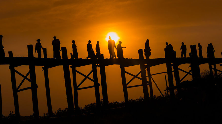 Silhouette people standing by bridge against sky during sunset