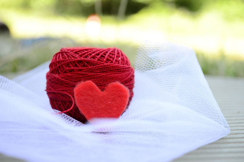 Close-Up Of Heart Shape By Red Thread Spool On White Tulle Netting