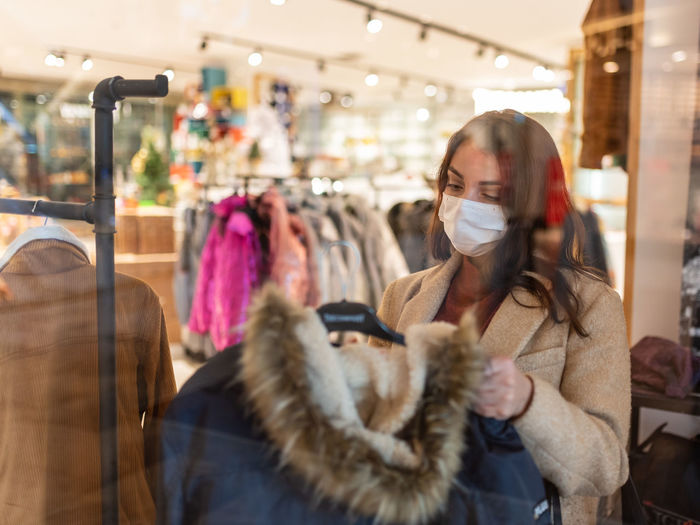 Woman choosing by rack in store