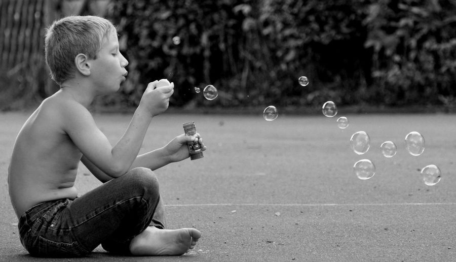 Shirtless boy blowing bubbles on road