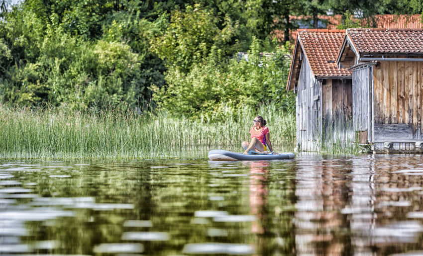 Woman relaxing on a standup paddle board Bavaria Bayern Calm Chiemsee Enjoy Germany Holiday Lake Meditation Moment Munich Nature Recreation  Relax Staffelsee Standup Paddleboarding Standuppaddle Standuppaddleboarding Summer Sup Surfer Tegernsee Tranquility Tranquility Woman