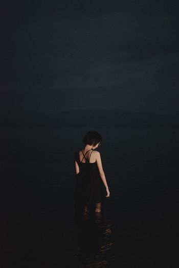 Full length of woman standing at beach against clear sky