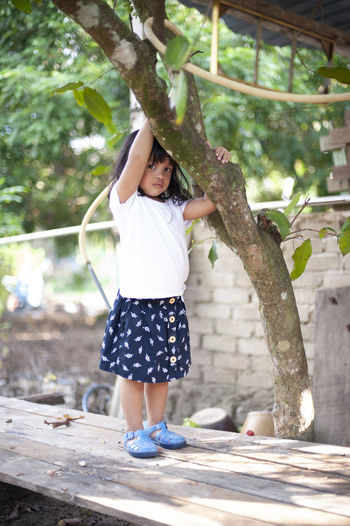Full Length Of Girl Standing By Tree On Wooden Table